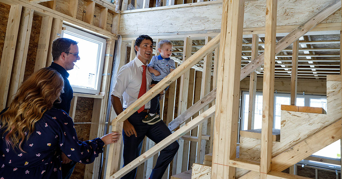 Justin Trudeau visting a housing development under construction in Vancouver. He his holding a child with his left arm
