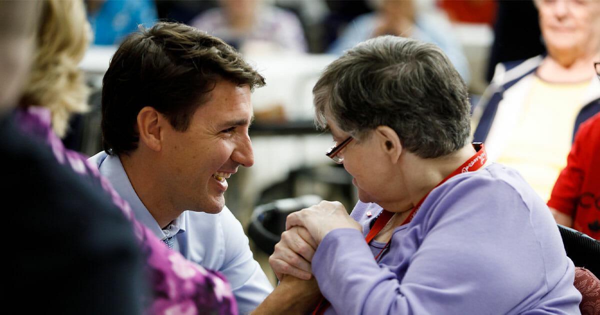 Justin Trudeau having a conversation with a senior