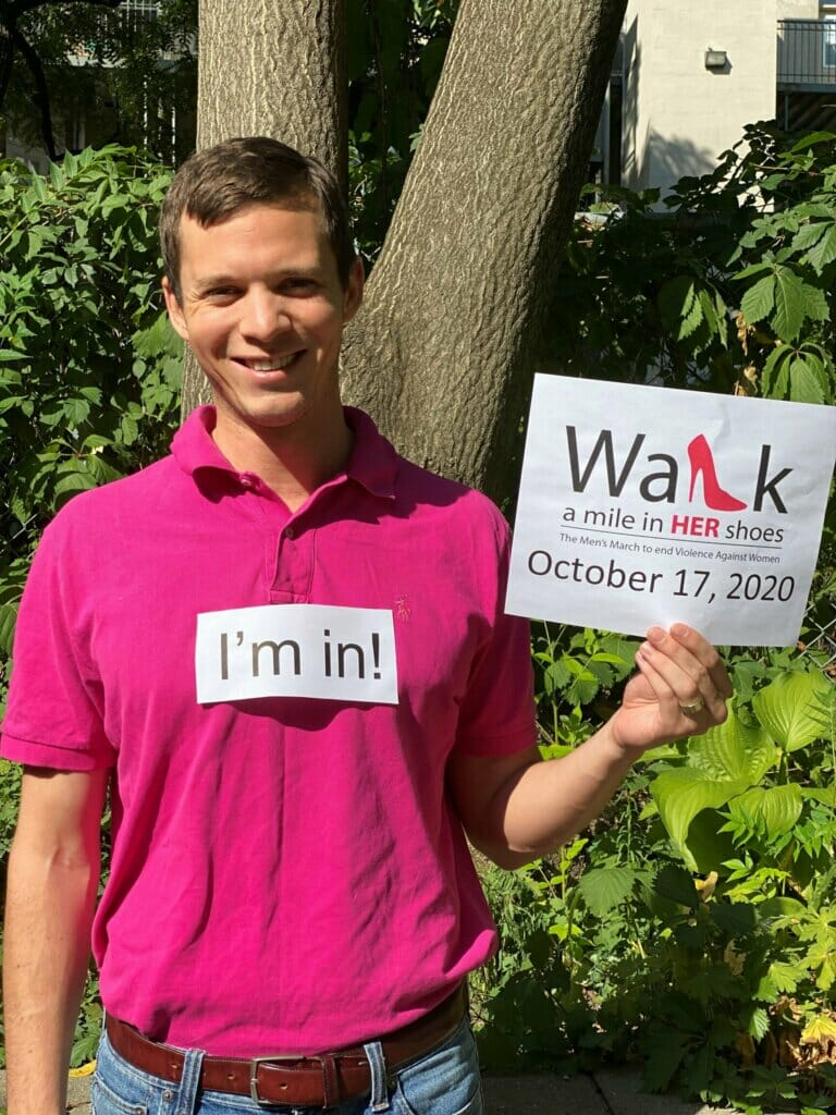Ian Bingam in a pink shirt holding a sign about Walk a mile in HER shoes event on October 17, 2020