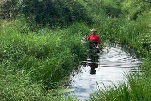 Leon Jensen wading in Bertrand Creek to help clean up